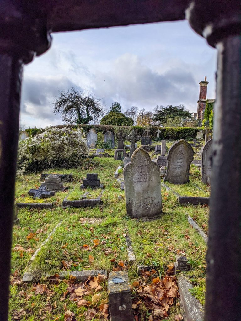 gravestones on a nice October day, viewed through the cast-iron perimeter fence