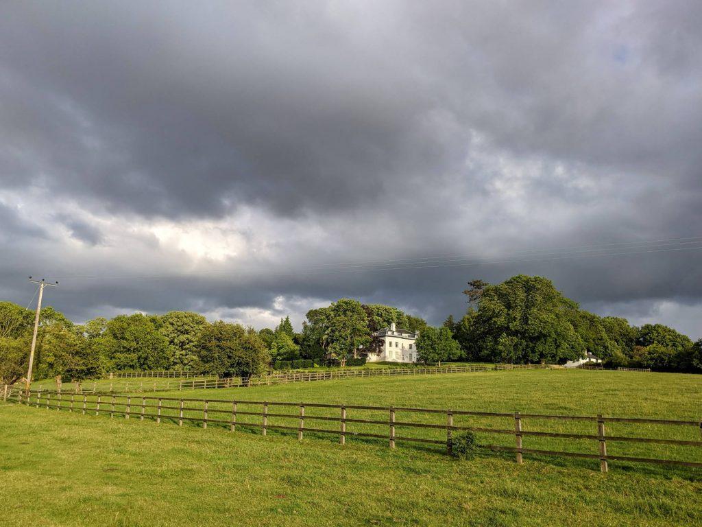 fields, house and dark sky